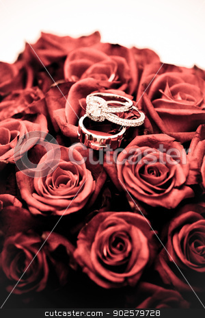 Wedding rings on a bouquet of roses stock photo, Wedding rings balanced on a bouquet of red roses, symbolic of everlasting love and commitment by JRstock