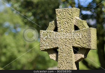 Celtic cross in cemetery stock photo, Celtic cross in cemetery with leafy green background. by Martin Crowdy