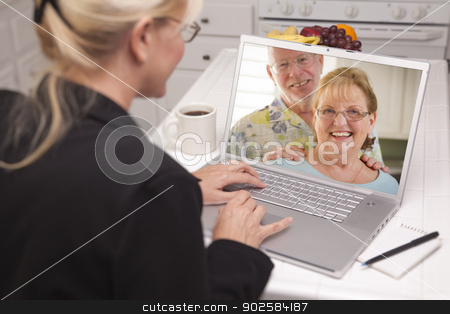 Woman In Kitchen Using Laptop - Online with Senior Couple stock photo, Woman In Kitchen Using Laptop - Online Chat with Senior Couple or Parents On Screen. by Andy Dean