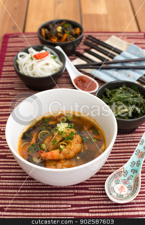 Asian soup with shrimps stock photo, Asian soup with shrimps in white ceramic bowl composed with ceramic spoon with spicy red sauce, asian chopsticks and black bowls with rice noodles, kale (green cabbage) and fried vegetables. Composition on a old styled wooden table. by doupix