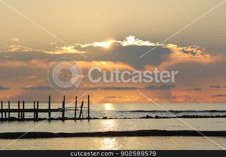 Sunrise over a wooden pier stock photo, Fiery sunrise over a wooden pier at a tropical resort in the Mayan Riviera, Mexico. by Monia Kosciejew