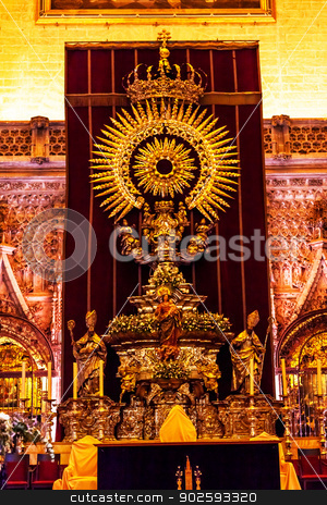 Golden Paseo Madonna Statue Cathedral of Saint Mary of the See S stock photo, Golden Paseo Madonna Statue Seville Cathedral, Cathedral of Saint Mary of the See, Seville, Andalusia Spain.  During Holy Week, Paseos are paraded around Seville, Spain on Wooden Floats in the Semana de Santa de Sevilla.  This is the Paseo for Seville, Cathedral. by William Perry