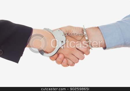 Business people in handcuffs shaking hands stock photo, Closeup of business people in handcuffs shaking hands against white background by Wavebreak Media