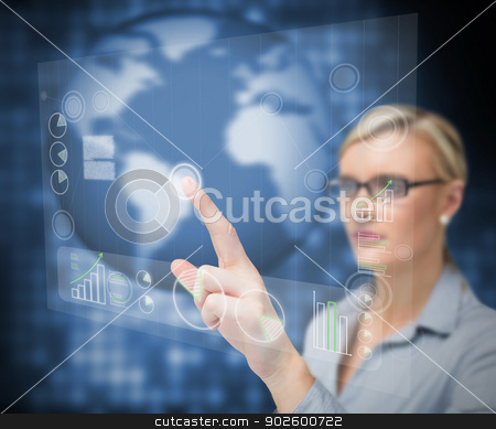 Businesswoman pointing touch screen stock photo, Businesswoman pointing touch screen against a blue background by Wavebreak Media
