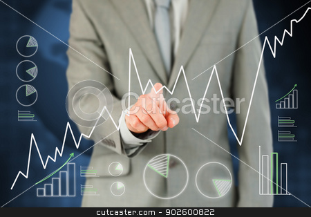 Man in suit pointing a curve on touch screen stock photo, Man in suit pointing a curve on touch screen against a background by Wavebreak Media