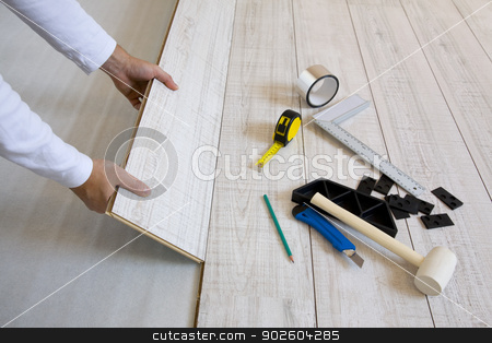 Worker laying laminated stock photo,  Worker laying a floor with laminated flooring boards  by Tilo