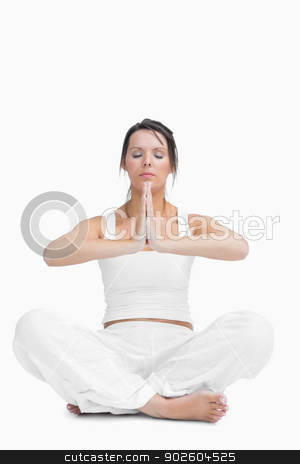 Young woman with crossed legs in praying position stock photo, Young woman with crossed legs in praying position over white background by Wavebreak Media