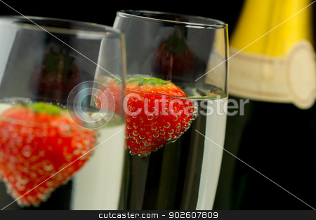 Strawberries floating in two champagne flutes stock photo, Strawberries floating in two champagne flutes with bottle in background by Wavebreak Media