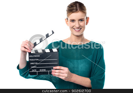 Young girl posing with clapperboard stock photo, Lights, camera, action. Young girl holding clapperboard by Ishay Botbol