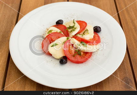 Delicious mozzarella, tomatoes salad stock photo, Delicious mozzarella, tomatoes salad in white plate on a wooden table. by doupix