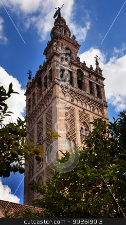 Giralda Bell Tower From Orange Garden Cathedral of Saint Mary of stock photo, Giralda Spire, Bell Tower, From Orange Garden, Seville Cathedral, Cathedral of Saint Mary of the See, Seville, Andalusia Spain.  Built in the 1500s.  Largest Gothic Cathedral in the World and Third Largest Church in the World.  Burial Place of Christopher Columbus.  Giralda is a former minaret converted into a bell tower by William Perry