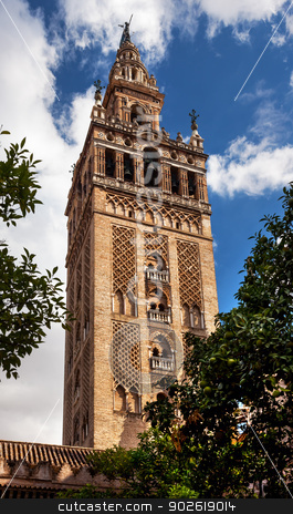 Giralda Bell Tower Cathedral of Saint Mary of the See Spire Weat stock photo, Giralda Spire, Bell Tower, From Orange Garden Seville Cathedral, Cathedral of Saint Mary of the See, Seville, Andalusia Spain.  Built in the 1500s.  Largest Gothic Cathedral in the World and Third Largest Church in the World.  Burial Place of Christopher Columbus.  Giralda is a former minaret converted into a bell tower by William Perry