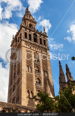 Giralda Bell Tower Cathedral of Saint Mary of the See Spire Weat stock photo, Giralda Spire, Bell Tower, Giraldillo Statue, Seville Cathedral, Cathedral of Saint Mary of the See, Seville, Andalusia Spain.  Giralda was built in 1184 as a minaret and in 1500s converted to a bell tower.   Largest Gothic Cathedral in the World and Third Largest Church in the World.  Burial Place of Christopher Columbus.  by William Perry