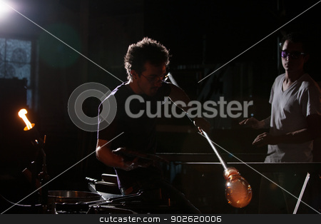 Person Manufacturing Glass stock photo, Man working with hot glass object and rod indoors by Scott Griessel