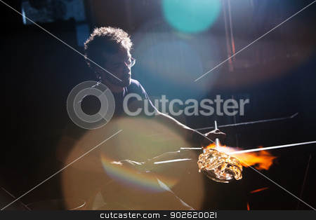 Worker Creating Vase in Dark stock photo, Lens flares surround glass worker creating vase by Scott Griessel