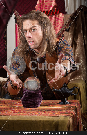 Gesturing Fortune Teller stock photo, Cute man with crystal ball and open hands by Scott Griessel