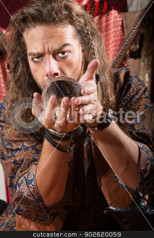 Man Looking into Crystal Ball stock photo, Serious Gypsy man coddling a crystal ball by Scott Griessel