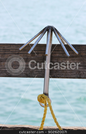 Hook stock photo, A Hook hanging on a board with the ocean in the background. by Henrik Lehnerer