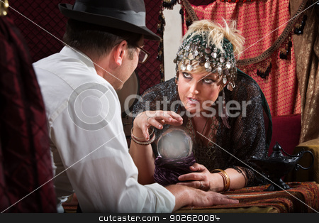 Fortune Teller with Crystal Ball stock photo, Pretty female fortune teller talking to customer over crystal ball by Scott Griessel