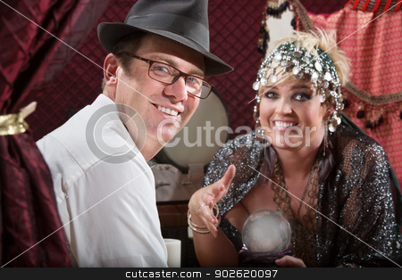 Smiling Fortune Customer stock photo, Happy gypsy fortune teller and man with glowing crystal ball by Scott Griessel