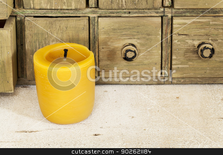 bee wax candle stock photo, bee wax candle in retro setting with a primitive apothecary drawer cabinet by Marek Uliasz
