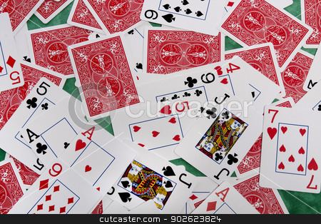 bunch of cards stock photo, Close up view of a bunch of playing cards spread on a green cloth table. by Mauro Rodrigues