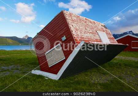 House disaster stock photo, Red wooden hut turned around by heavy storm on Lofoten islands in Norway by Harvepino
