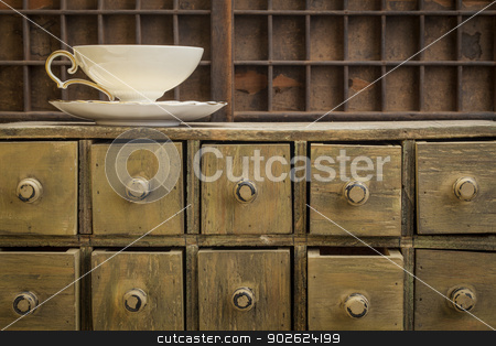 classic tea cup stock photo, classic tea cup on top of rustic apothecary drawer cabinet by Marek Uliasz