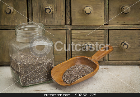jar and scoop of chia seeds stock photo, jar and scoop of chia seeds with a primitive apothecary drawer cabinet by Marek Uliasz