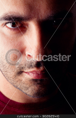 male man with serious look stock photo, Close detail view of a young male man with a serious look isolated on a black background. by Mauro Rodrigues