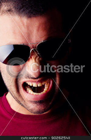 angry male man stock photo, Close detail view of a angry young male man with dark shades isolated on a black background. by Mauro Rodrigues