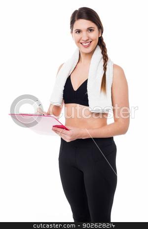 Fit lady trainer preparing diet chart stock photo, Slim female gym trainer preparing diet chart by Ishay Botbol