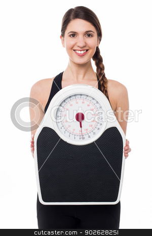 Young girl holding weighing machine stock photo, Charming young female displaying weighing machine by Ishay Botbol