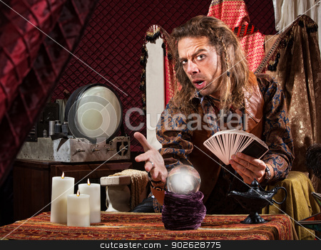 Enticing Fortune Teller stock photo, Enticing man with tarot cards and crystal ball by Scott Griessel