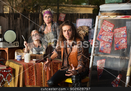 Angry Man with Fortune Tellers stock photo, Angry man at table with female fortune tellers by Scott Griessel