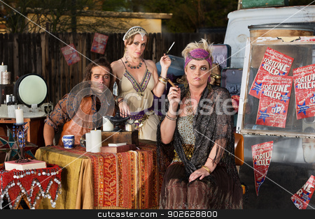 Serious Fortune Tellers stock photo, Trio of serious fortune tellers sitting outside with table by Scott Griessel