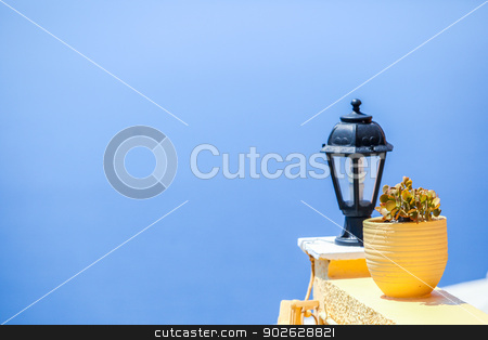 Traditional greek details: colorful flowers with pots, lantern and caldera sea in background stock photo, Traditional greek details: colorful flowers with pots, lantern and caldera sea in background by Dmitry Travnikov