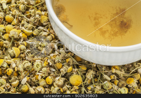 chamomile herbal tea stock photo, a cup of chamomile herbal tea with background of dry flowers by Marek Uliasz