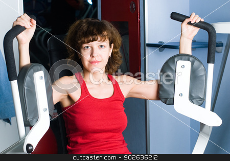 Training girl stock photo, Young woman on training apparatus in fitness center by Aikon
