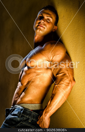 Handsome young bodybuilder against wall stock photo, Attractive and muscular male bodybuilder leaning against yellow wall smiling by Stefano Cavoretto