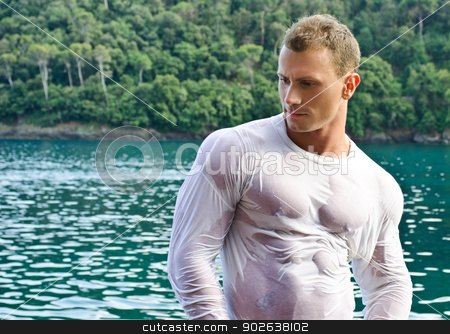 Handsome young bodybuilder by the sea with wet shirt on stock photo, Attractive young bodybuilder by the sea with wet shirt on, serious expression by Stefano Cavoretto