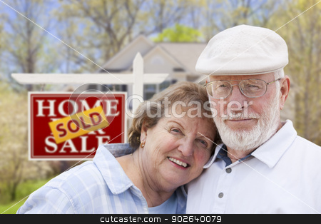 Senior Couple in Front of Sold Real Estate Sign and House stock photo, Happy Affectionate Senior Couple Hugging in Front of Sold Real Estate Sign and House. by Andy Dean