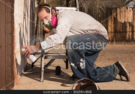Kneeling Graffiti Artist stock photo, Kneeling graffiti artist with spray paint can and respirator by Scott Griessel