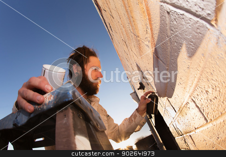 Artist Creating Mural stock photo, Male graffiti artist creating mural on wall by Scott Griessel