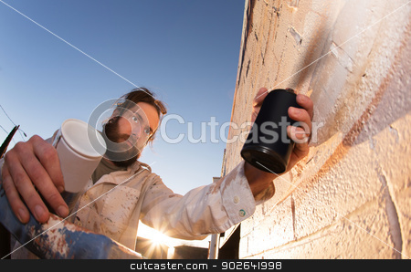 Wall Painting Artist Working stock photo, Serious male spray paint artist working with can by Scott Griessel