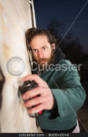 Man with Beard Spray Painting stock photo, Man with beard and mustach spray painting wall by Scott Griessel