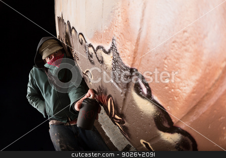Vandal Painting on Wall stock photo, Hooded vandal spray painting on wall outdoors by Scott Griessel