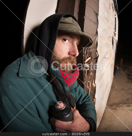 Spray Paint Vandal Near Wall stock photo, Criminal man with spray paint can next to a wall by Scott Griessel