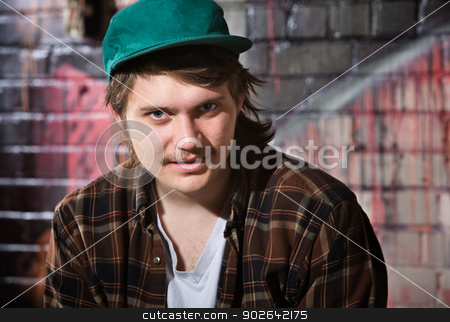 Young Urban Youth stock photo, Young Caucasian man in flannel shirt sitting outside by Scott Griessel