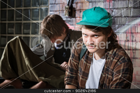 Frustrated Homeless Youth stock photo, Frustrated young homeless man with friend sitting outside by Scott Griessel